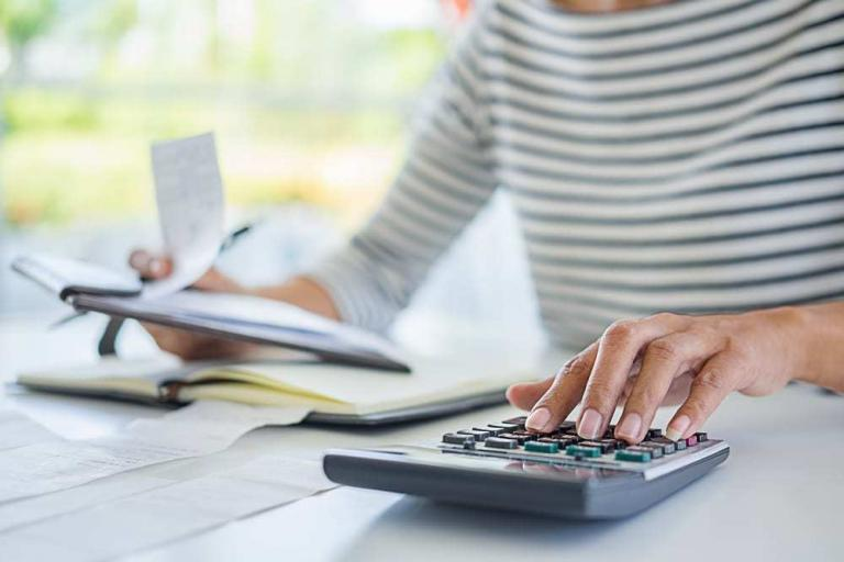 close-up of woman reviewing finances using calculator