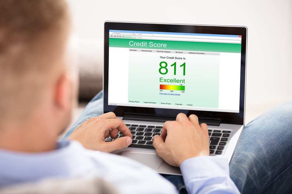 man checking excellent credit score with laptop