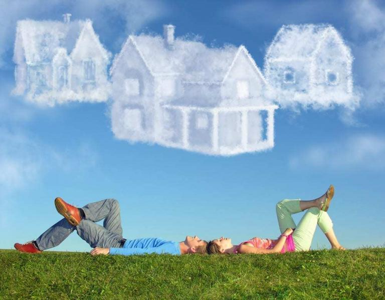 Couple lying on backs outside, clouds in the shape of homes above