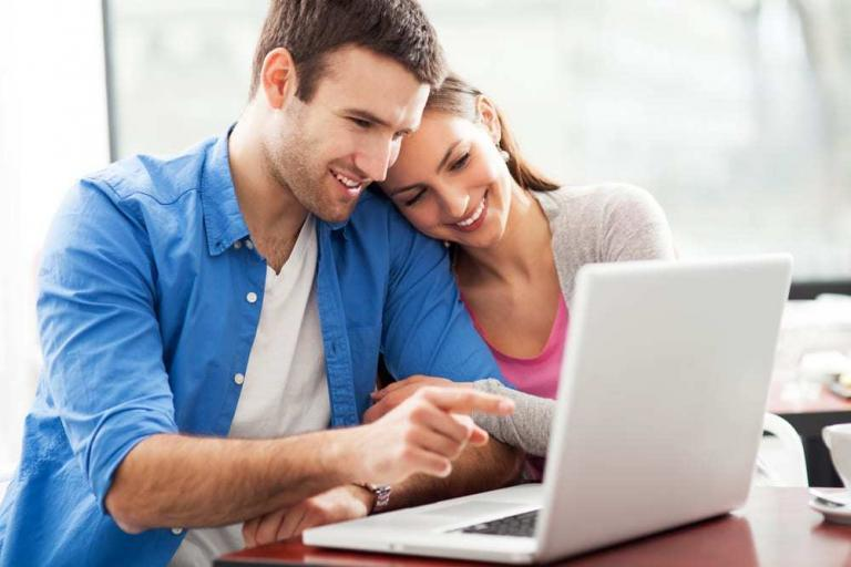 Young couple smiling and looking at laptop