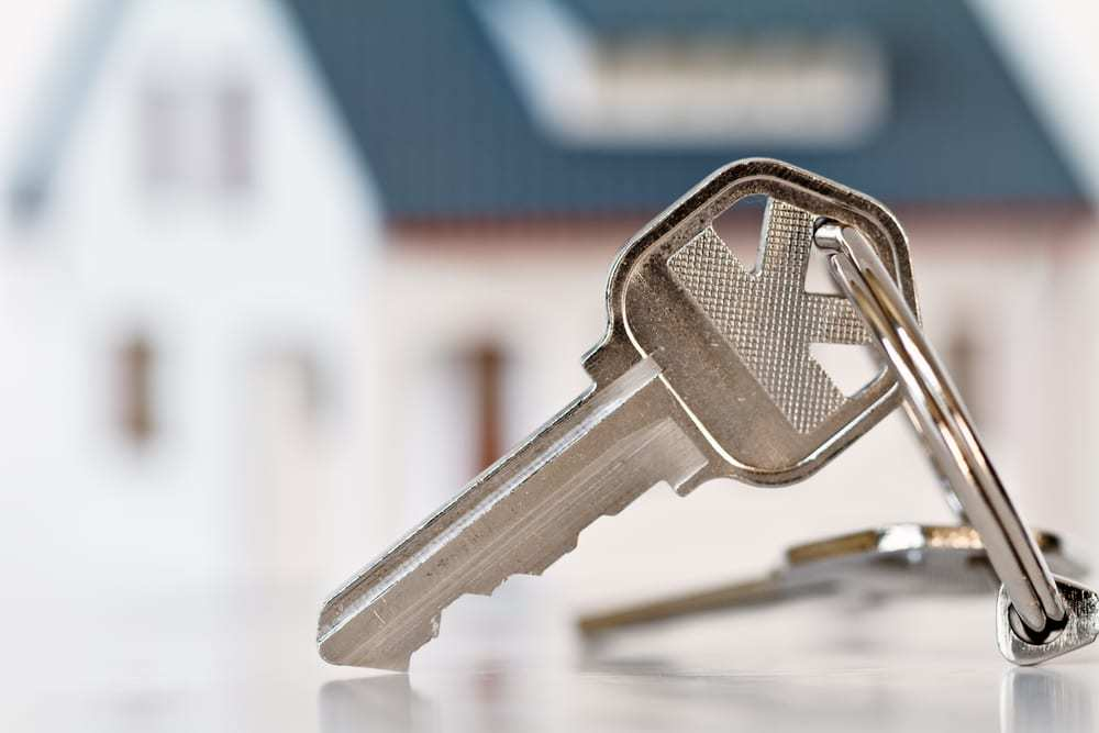 close-up of key in front of house