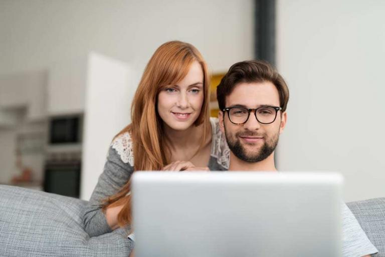 Young Couple Looking at Laptop at Home, Smiling