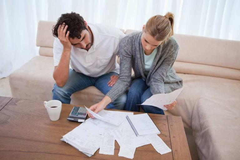 Stressed couple reviewing their finances