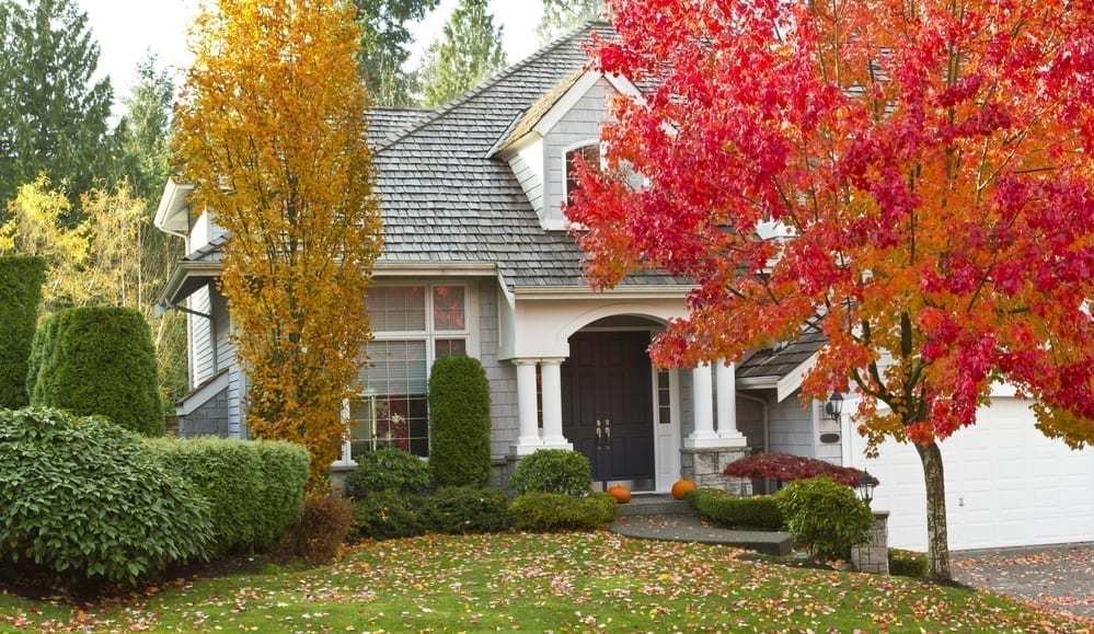 Beautiful home in fall, colorful leaves, pumpkins on patio