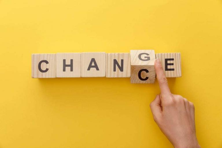 Yellow background, wooden blocks reading CHANGE, hand change it to CHANCE