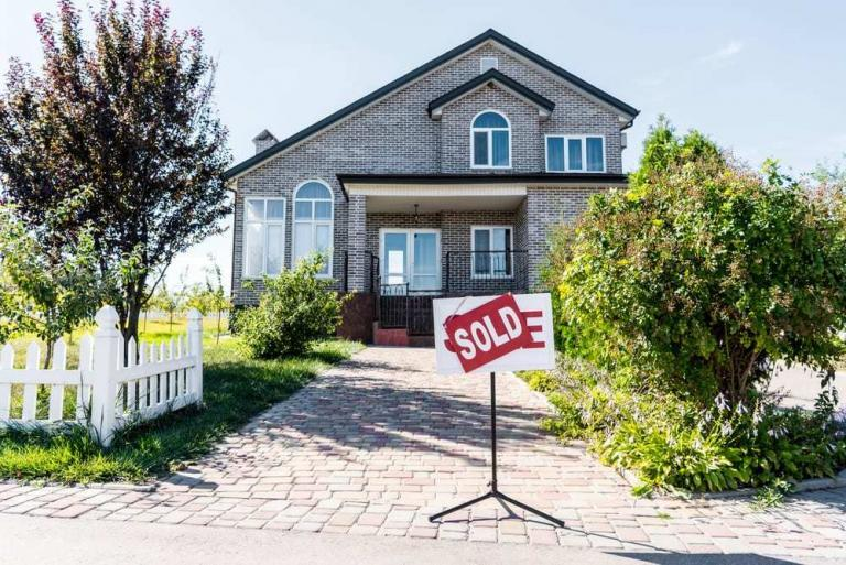 beautiful home with sold sign displayed in front