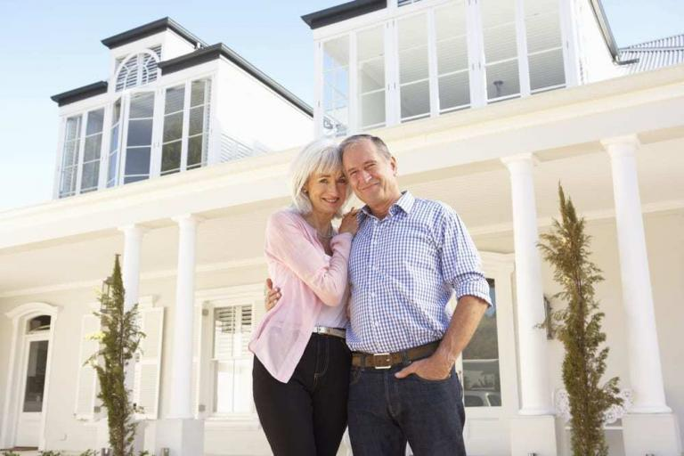 Senior couple embracing and smiling at camera in front of beautiful home