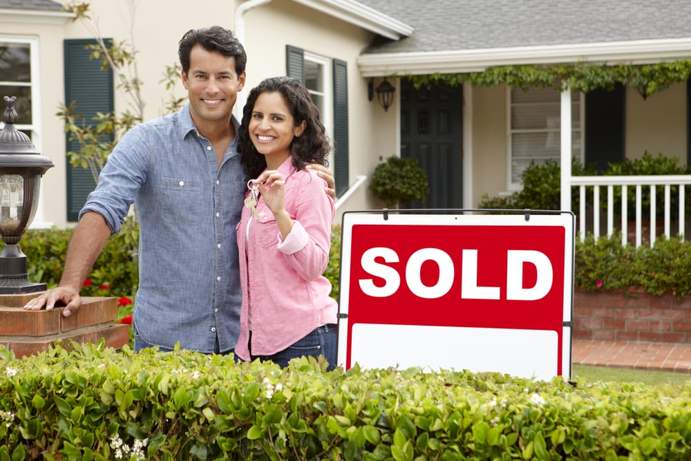 """Happy young couple standing by """"sold"""" sign in front of house"""