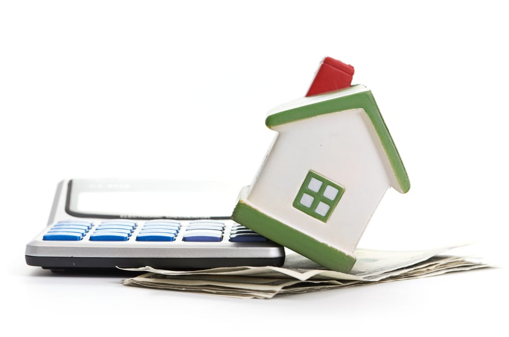 Small house model sitting on calculator and cash