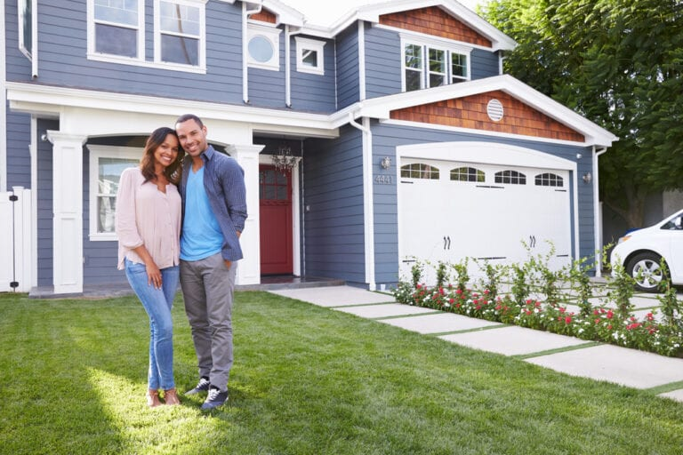 Smiling young couple standing in front of house