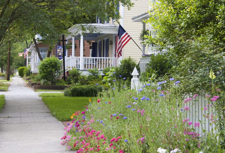 American flag hanging from front of house, flowers and sidewalk beyond