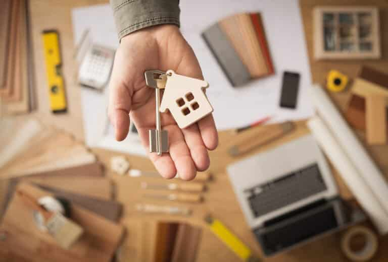 Hand holding out house key over a background of renovation tools