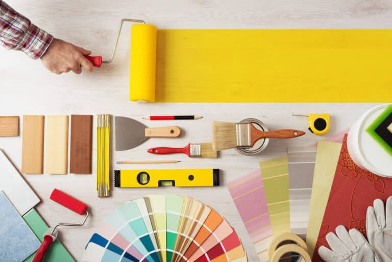 renovation tools laid on flat surface, hand painting yellow stripe with roller
