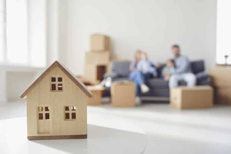 Wooden house model in front of family on couch surrounded by cardboard moving boxes