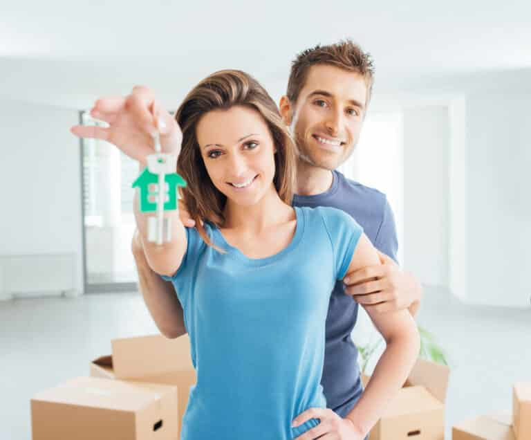 Young smiling couple holding out a house key