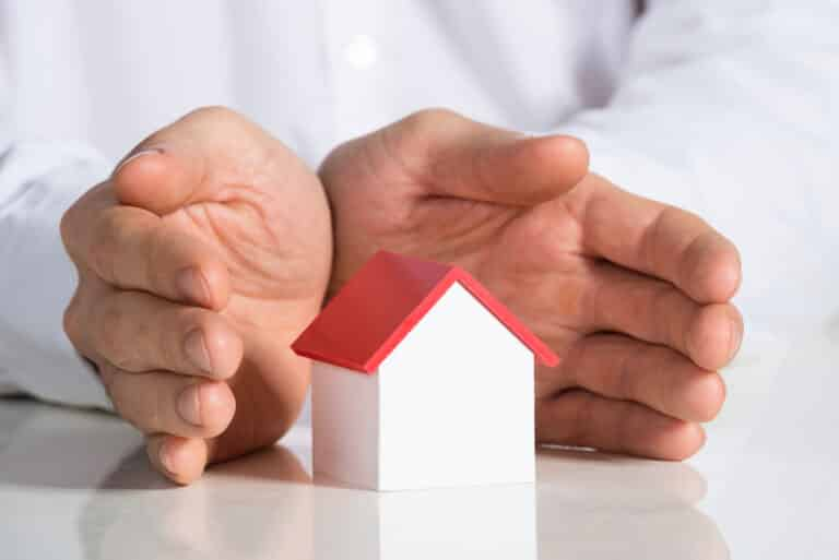 Close-up of hands shielding tiny house model