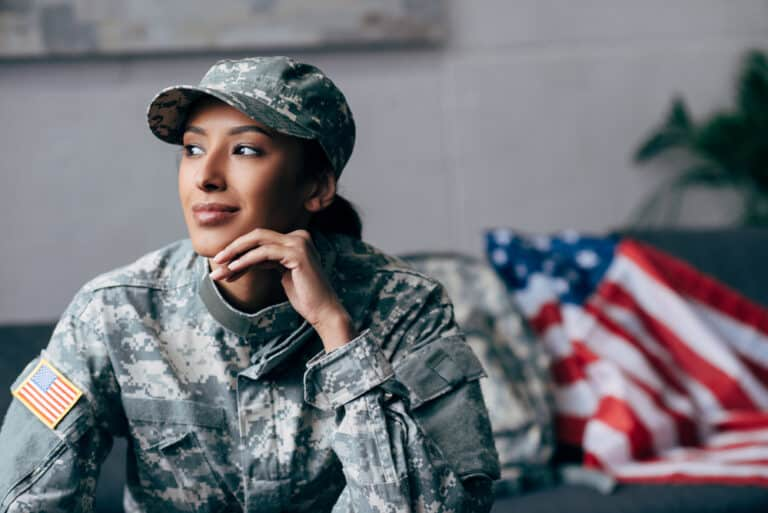 Young woman in USA military uniform with thoughtful expression, American flag on couch beside her