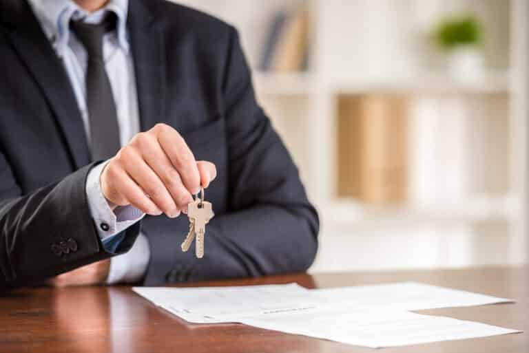 Man in suit holding out housekeys, contract on desk